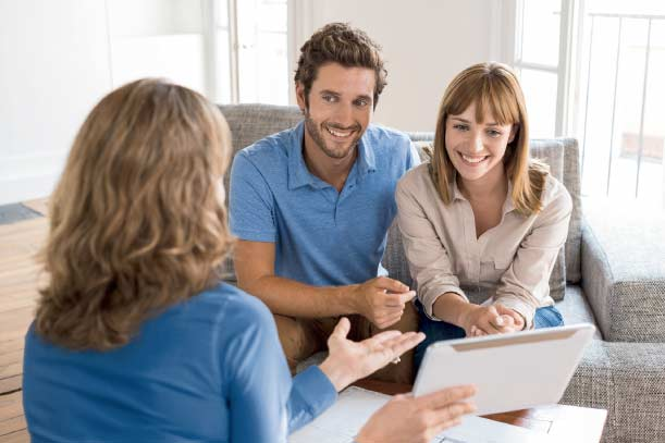 woman salesperson helping young couple in their home
